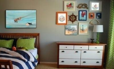 Boys room with a collage of artwork on the wall. Give children art they can relate to.