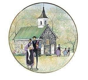 Season of Faith Spring Ornament by P Buckley Moss features a couple with baby in arms in front of a church with colors of cream, cream, gray white and a splash of lavender and black.