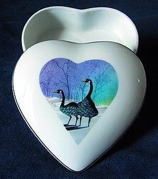 Geese Heart Shaped Porcelain Keepsake Box by P Buckley Moss. Two geese in heart-shaped background in purple and turquoise on a white box.