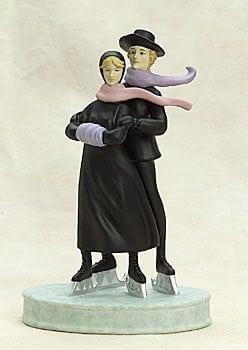 Skating couple on the figurine base with scarves flowing in a skating embrace. Colors of light green and pink, lavender and black.