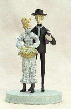 Together Forever porcelain figurine by P Buckley Moss featuring a wedding couple on a base with the woman carrying a basket of flowers, man carrying a bible. Colors of light green and pastel colors with black coat.