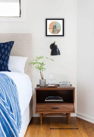 How do you hang art? Shown above a bedside night table.