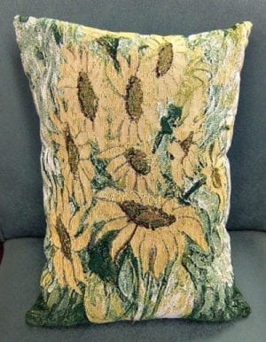 Golden sunflowers adorn this vertical pillow. Muted golden sunflowers with multicolored greenery.