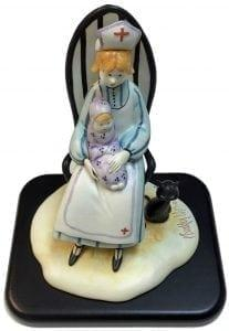 Nurse Figurine titled Loving Care is a P Buckley Moss figurine featuring a nurse holding a baby and giving comfort. Colors of lavender, blue, cream, golden for hair and black base and tiny cat.