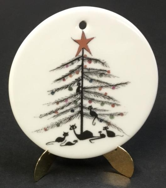 Purrfect Christmas porcelain ornament by P Buckley Moss. White background with black limbs on the tree and black cats under the tree. A few colored ornaments on the tree.